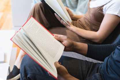 man reading book beside woman reading book